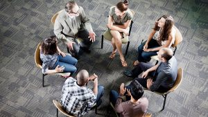 A group of people formed a circle that seems to be discussing something. It might be a group therapy session