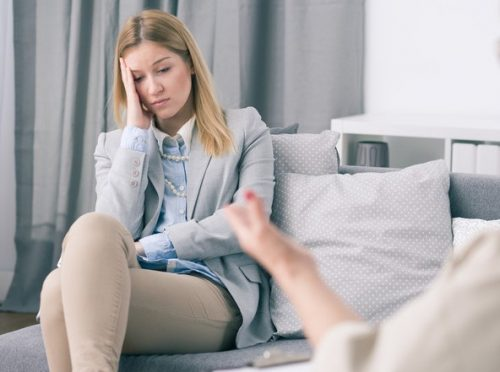 A woman sitting on a couch looking anxious while someone seems to be talking to her. Maybe she is talking to a therapist.