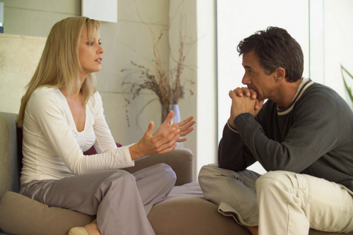 A woman talking to the man infront of her. The man is fervently listening to what the woman is saying.